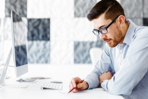 male office worker sitting at desk looking at report