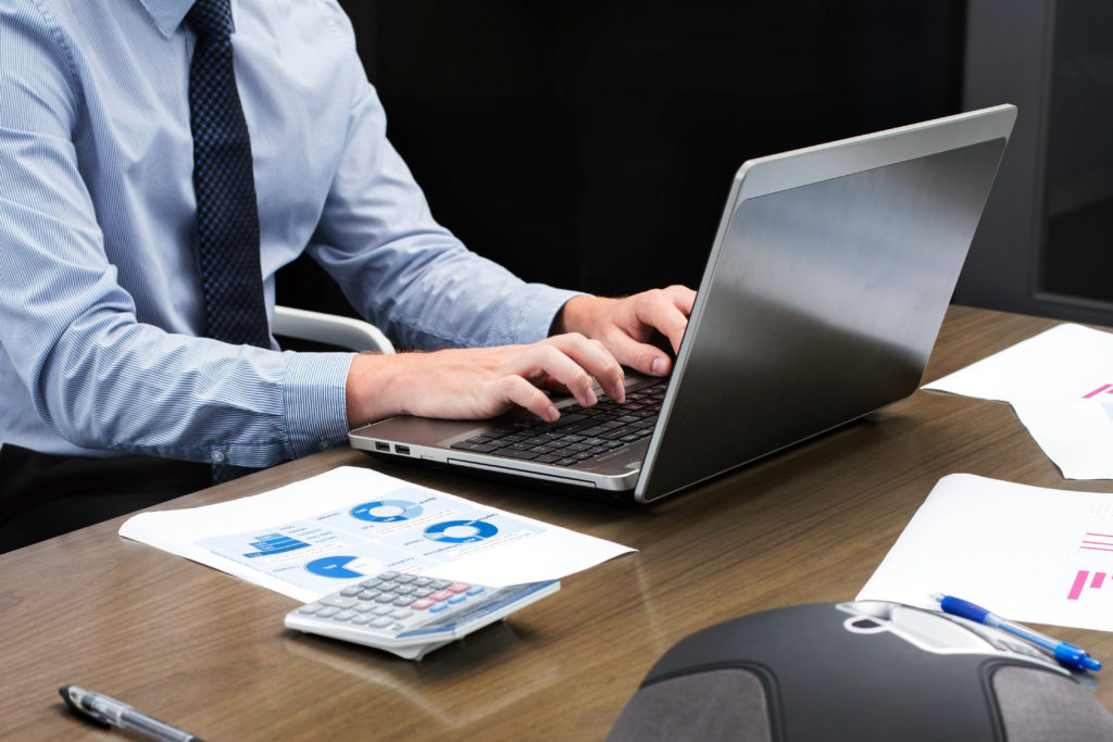Office person typing on laptop
